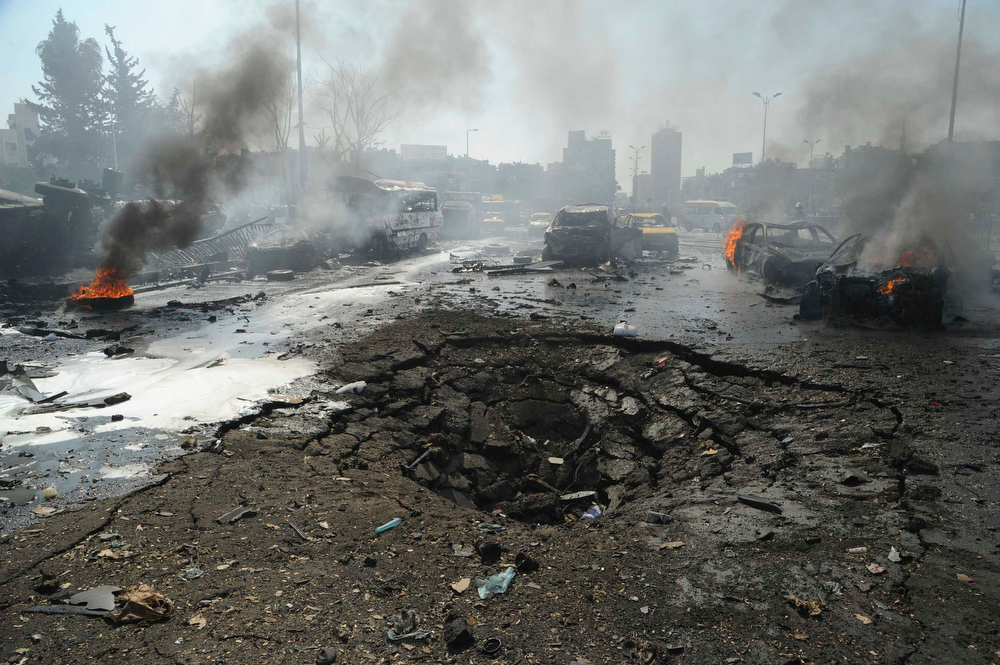 Description of . Vehicles burn near a crater on a road after an explosion at central Damascus February 21, 2013, in this handout photograph released by Syria's national news agency SANA. The big explosion shook the central Damascus district of Mazraa on Thursday, residents said, and Syrian state media blamed what it said was a suicide bombing on
