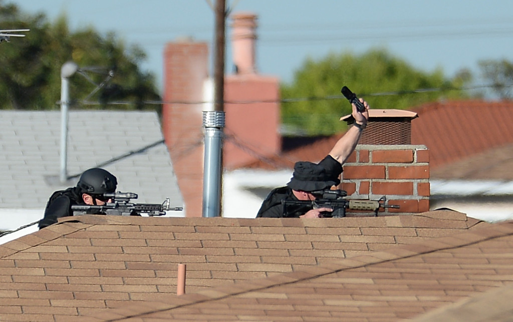 . A man allegedly shot an Inglewood police officer Wednesday, November 27, 2013, in Inglewood, CA, and the took hostages as he barricaded inside a house on S. 5th Avenue.  Snipers take aim from the a rooftop on a home on 6th Ave. Photo by Steve McCrank/DailyBreeze