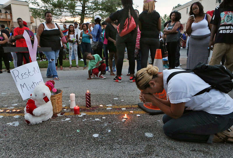 . Meghan O\'Donnell, 29, from St. Louis, prays at the spot where Michael Brown was killed Sunday evening, Aug. 10, 2014, in Ferguson, Mo. A few thousand people have crammed the street where a black man was shot multiple times by a suburban St. Louis police officer. The candlelight vigil Sunday night was for 18-year-old Michael Brown, who died a day earlier. Police say he was unarmed. (AP Photo/St. Louis Post-Dispatch, J.B. Forbes)