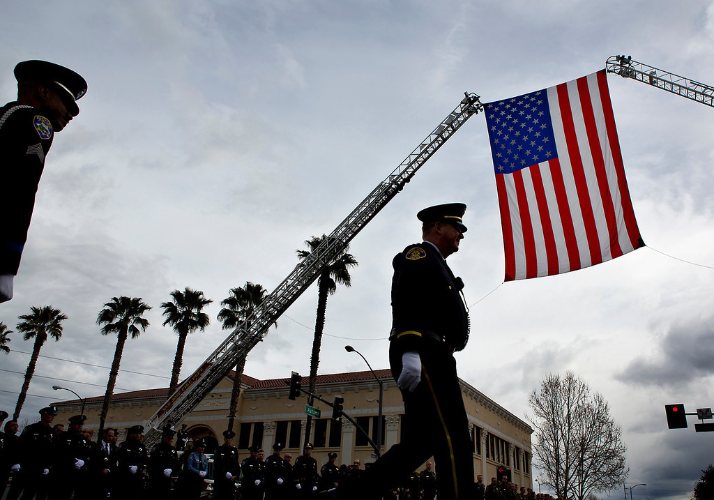 . Police officers from across the Central Valley gathered in mass underneath a large American  Flag outside of the HP Pavilion in San Jose on Thursday as limousines carrying the family members of SCPD detectives Sgt. Loran \'Butch\' Baker and Elizabeth Butler. (Kevin Johnson/Sentinel)