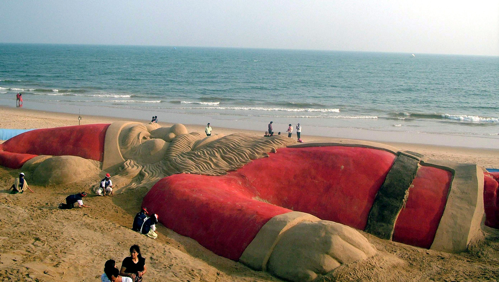 Description of . Students join sand sculpture artists to create a 30-meter-long (100-foot-long) Santa Claus sculpture on the Puri golden beach, in the Indian state of Orissa on the eve of Christmas, Sunday, Dec. 24, 2006. Though Hindus and Muslims comprise the majority of the population in India, Christmas is celebrated with much fanfare. (AP Photo/Biswaranjan Rout)