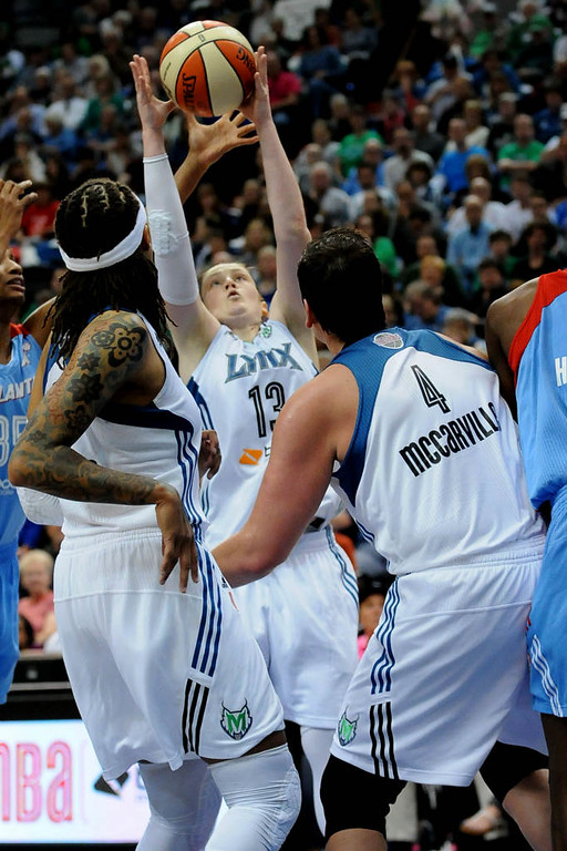 . Minnesota guard Lindsay Whalen snags a rebound as teammates Seimone Augustus, left, and Janel McCarville watch during the fourth quarter. (Pioneer Press: Sherri LaRose-Chiglo)
