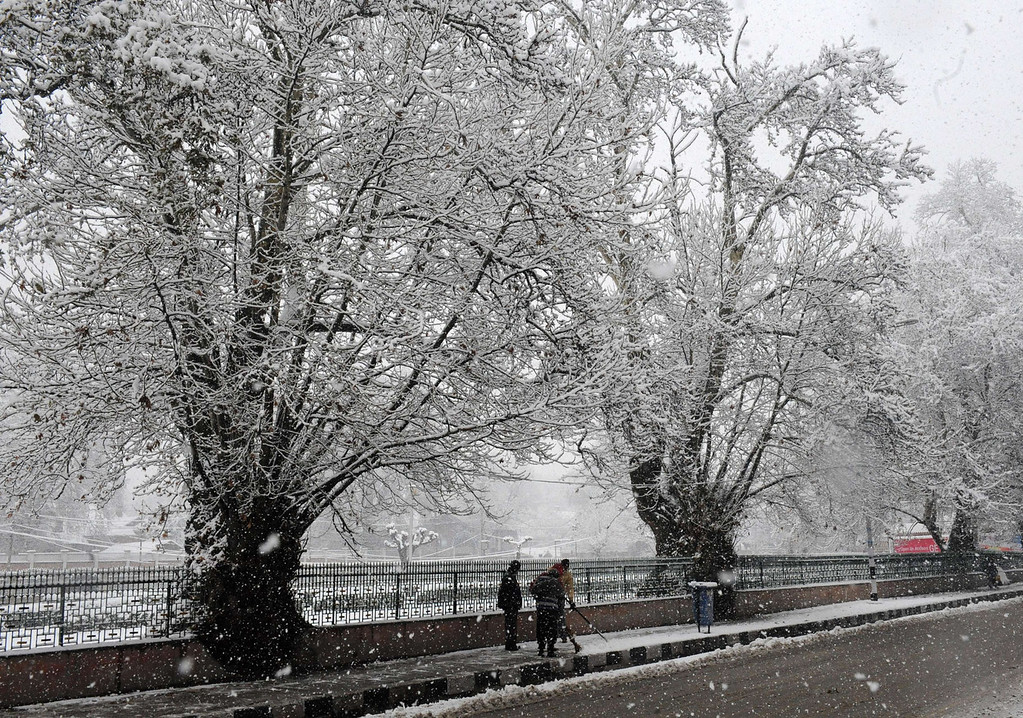 . Municipal workers clear a sidewalk during a snowfall in Srinagar on December 31, 2013. A cold wave further tightened its grip in Jammu and Kashmir with most places in the state recording sub-zero temperatures. ROUF BHAT/AFP/Getty Images
