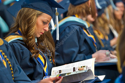 7. Students looking at their diplomas together in their seats.