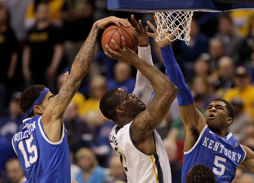 . Wichita State\'s Chadrack Lufile (0) shoots under pressure from Kentucky\'s Willie Cauley-Stein (15) and Andrew Harrison (5) during the first half of a third-round game at the NCAA college basketball tournament Sunday, March 23, 2014, in St. Louis. (AP Photo/Charlie Riedel)