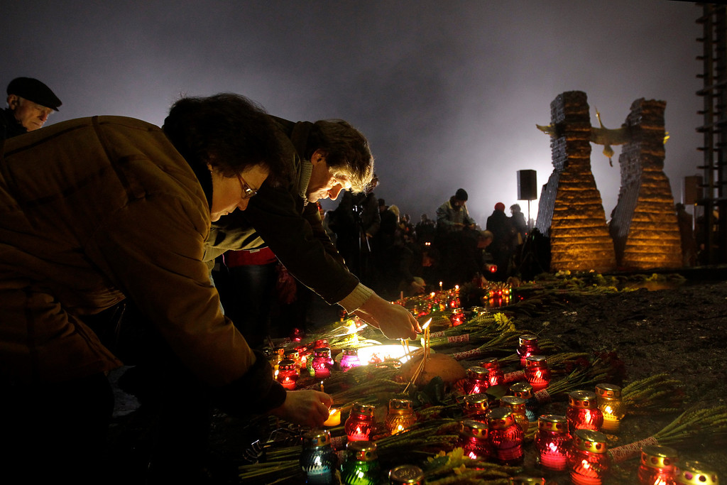 . People light candles during a ceremony to commemorate victims of the 1932-33 Great Famine in Kiev, Ukraine, Saturday, Nov. 23, 2013. (AP Photo/Sergei Chuzavkov)
