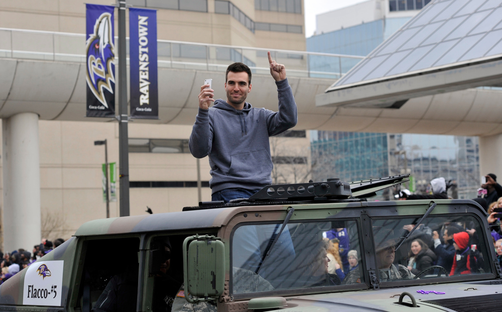 Description of . Baltimore Ravens quarterback and Super Bowl MVP Joe Flacco gestures while riding in a Humvee during the Ravens victory parade Tuesday, Feb. 5, 2013, in Baltimore. The Ravens defeated the San Francisco 49ers in NFL football's Super Bowl XLVII 34-31 on Sunday. (AP Photo/Gail Burton)