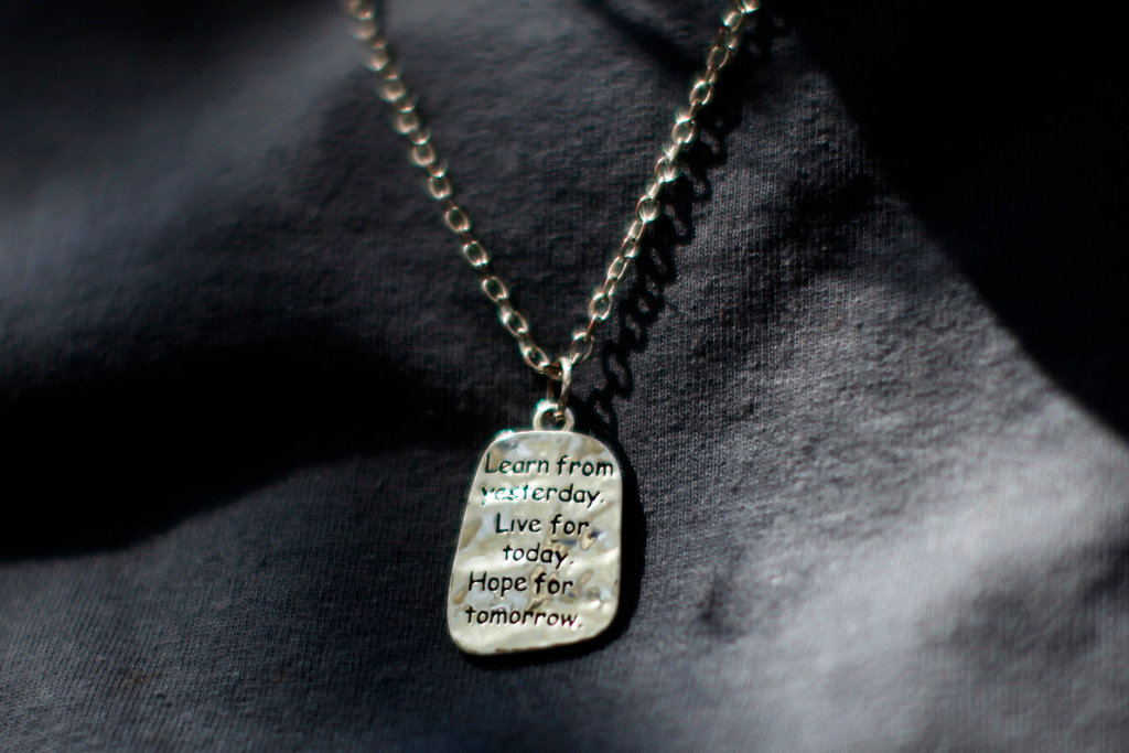 """. A woman wears a pendant inscribed with \""""Learn from yesterday, live for today, hope for tomorrow\"""" at Prototypes residential treatment program in Pomona, California, March 26, 2013. Prototypes is part of the Second Chance Women\'s Re-entry Court program, one of the first in the U.S. to focus on women. It offers a cost-saving alternative to prison for women who plead guilty to non-violent crimes and volunteer for treatment. Of the 297 women who have been through the court since 2007, 100 have graduated, and only 35 have been returned to state prison. Picture taken March 26, 2013. REUTERS/Lucy Nicholson"""