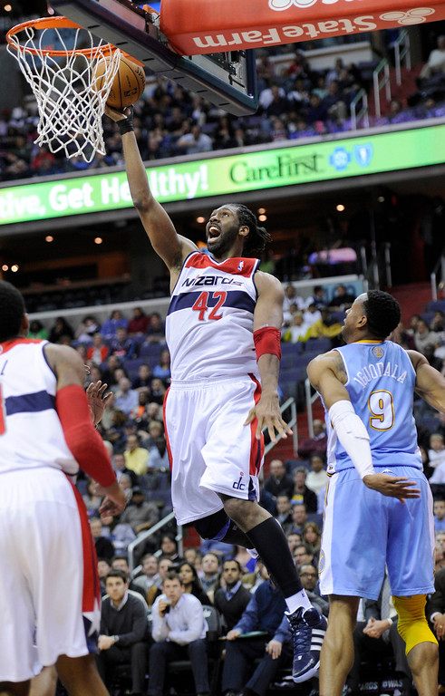 . Washington Wizards center Nene (42), of Brazil, goes to the basket against Denver Nuggets guard Andre Iguodala (9) during the second half of an NBA basketball game, Friday, Feb. 22, 2013, in Washington. The Wizards won 119-113. (AP Photo/Nick Wass)