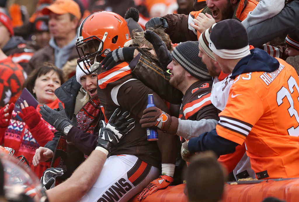 . Cleveland Browns running back Isaiah Crowell (34) is mobbed by fans after a four yard touchdown in the first half of an NFL football game against the San Diego Chargers, Saturday, Dec. 24, 2016, in Cleveland. (AP Photo/Aaron Josefczyk)
