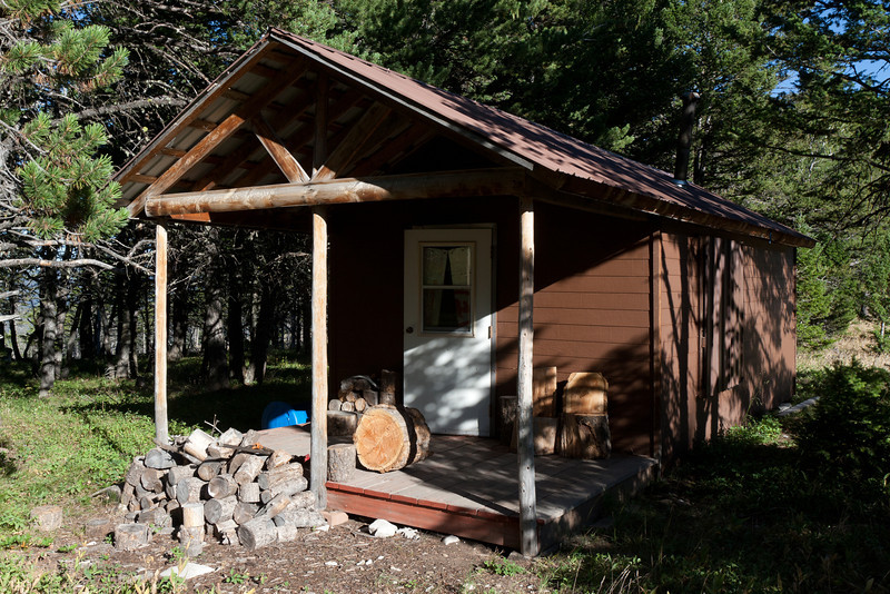 The cabin next to the picnic space.  Note the tree trunk chairs on the deck.