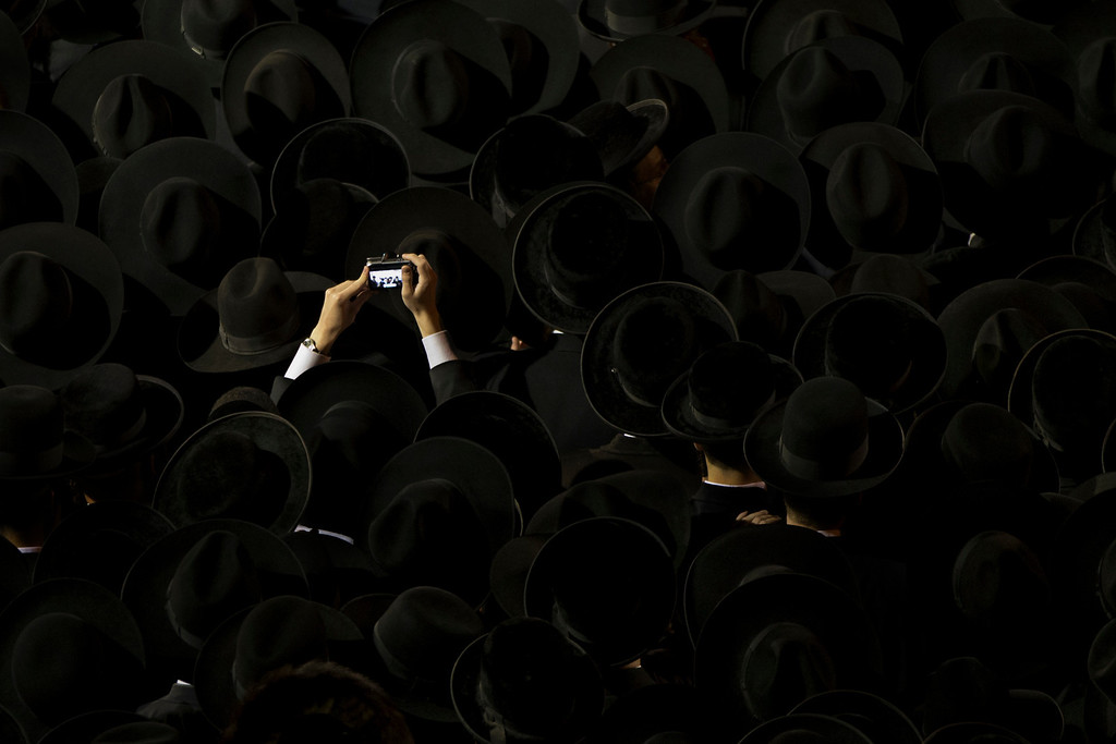 . An ultra-orthodox jew takes a snapshot during a protest against military conscription of yeshiva students, in Jerusalem, Thursday, May 16, 2013. (AP Photo/Bernat Armangue)