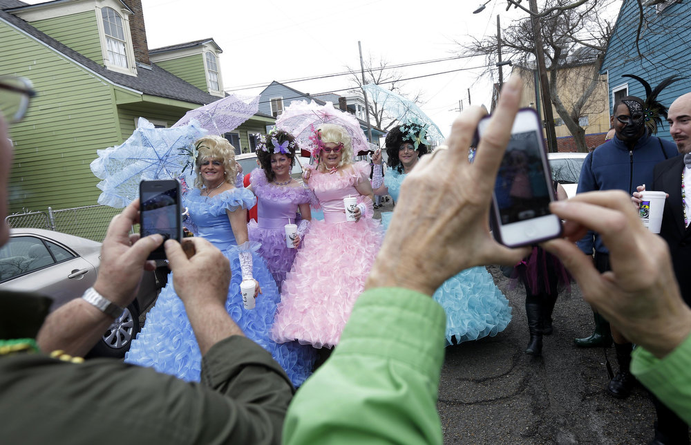 . Revelers gather and are photographed before the start of the Society of Saint Anne walking parade in the Bywater section of New Orleans during Mardi Gras day, Tuesday, Feb. 12, 2013. Overcast skies and the threat of rain couldn\'t dampen the revelry of Mardi Gras as parades took to the streets, showering costumed merrymakers with trinkets of all kinds.  (AP Photo/Gerald Herbert)