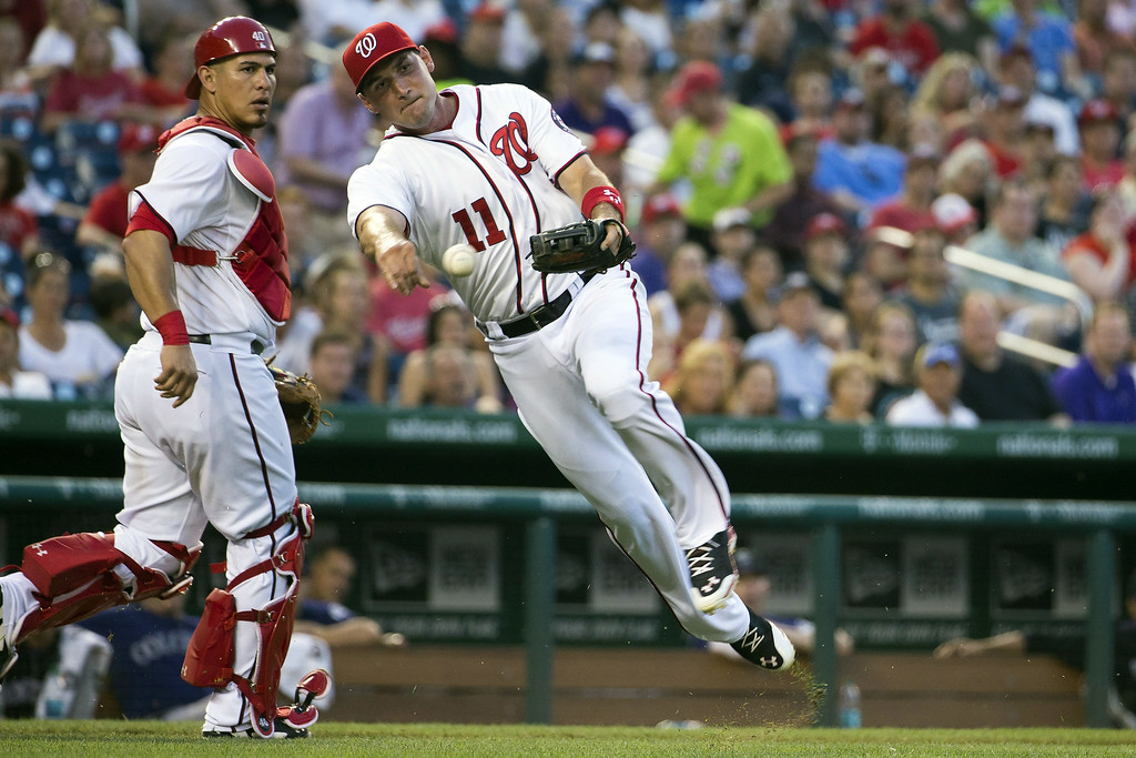 . Washington Nationals catcher WIlson Ramos, left, looks on as third baseman Ryan Zimmerman fields a bunt for a base hit by Colorado Rockies Brandon Barnes during the fifth inning of a baseball game at Nationals Park, on Monday, June 30, 2014, in Washington. (AP Photo/Evan Vucci)