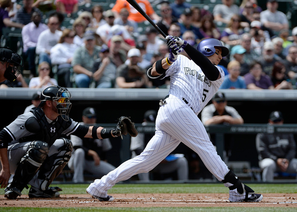 . Colorado Rockies outfielder, Carlos Gonzalez, hits a single against Tyler Flowers, left, and the Chicago White Sox at Coors Field Wednesday afternoon, April 09, 2014. (Photo By Andy Cross / The Denver Post)