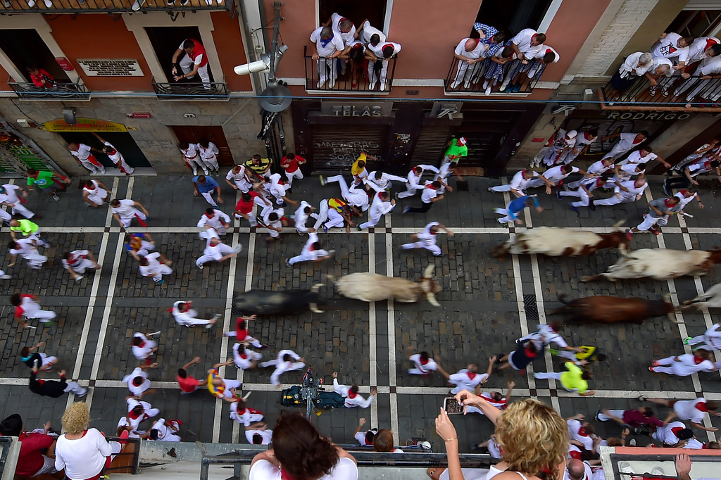 . Revellers run next to fighting bulls from the Cebada Gago ranch and steers during the third day of the running of the bulls at the San Fermin Festival in Pamplona, northern Spain, Monday, July 9, 2018. Revellers from around the world flock to Pamplona every year to take part in the eight days of the running of the bulls. (AP Photo/Alvaro Barrientos)