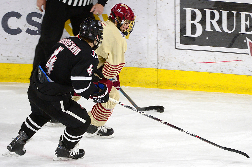. Denver Pioneers forward Emil Romig (18) holds off Nebraska-Omaha Mavericks defenseman Luc Snuggerud (4) on his way to set up for a goal during the second period at Magness Arena on March 4, 2016 in Denver, Colorado. (Photo by Brent Lewis/The Denver Post)