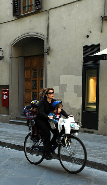 How do Italian women manage to look so elegant while riding a bike?  Notice she has TWO children with her!