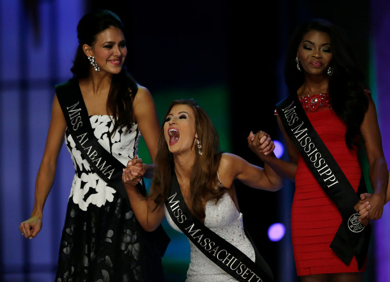 . Miss Massachusetts Lauren Kuhn, center, celebrates, while holding the hands of Miss Alabama Caitlin Brunell, left, and Miss Mississippi Jasmine Murray after advancing to the final round of the Miss America 2015 pageant, Sunday, Sept. 14, 2014, in Atlantic City, N.J. (AP Photo/Julio Cortez)