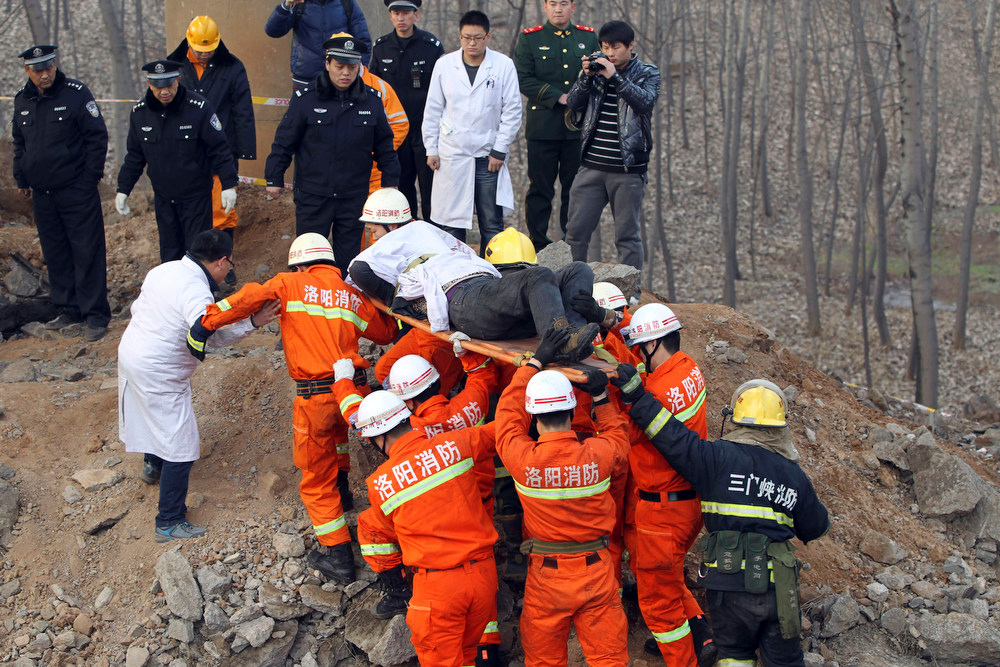 Description of . Rescuers remove a person who appears to be dead from an accident site where an expressway bridge partially collapsed due to a truck explosion in Mianchi County, Sanmenxia, central China's Henan Province, Thursday, Feb. 1, 2013. Fireworks for Lunar New Year celebrations exploded on a truck in central China, destroying part of an elevated highway Friday and sending vehicles plummeting 30 meters (about 100 feet) to the ground. State media had conflicting reports on casualties. (AP Photo)
