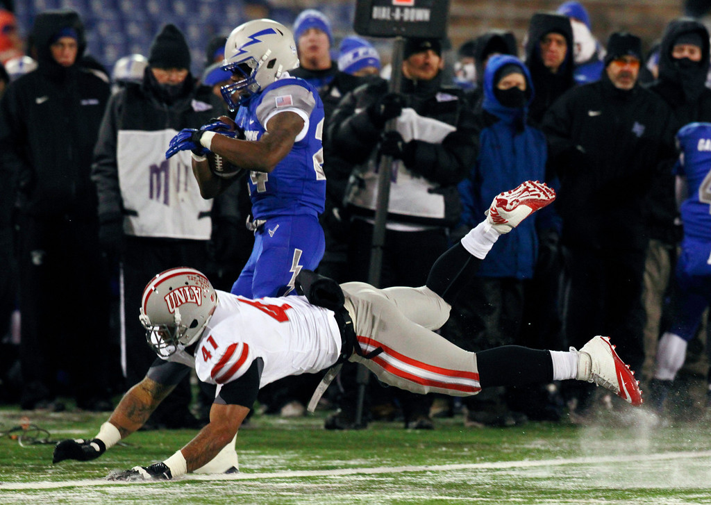 . UNLV linebacker Tani Maka, front, pushes Air Force running back Jon Lee out of play after a short gain in the second quarter of an NCAA football game at Air Force Academy, Colo., on Thursday, Nov. 21, 2013. (AP Photo/David Zalubowski)