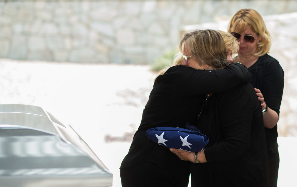 . Family members comfort each other besides the casket at Riverside National Cemetery in Riverside, Calif. on Tuesday, May 19, 2015. (Photo by Watchara Phomicinda/ Los Angeles Daily News)