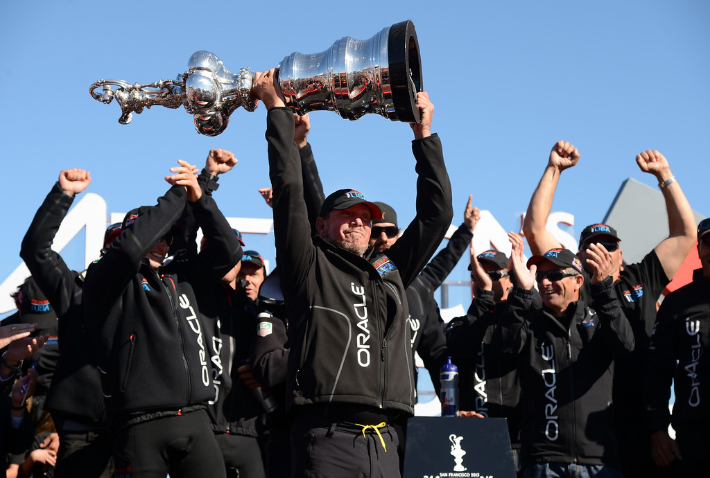 . Larry Ellison raises the America\'s Cup trophy after his Oracle Team USA overcame an unprecedented 8-1 deficit to defeat Emirates Team New Zealand in the 34th America\'s Cup Wednesday, Sept. 25, 2013, in San Francisco, Calif. (Karl Mondon/Bay Area News Group)