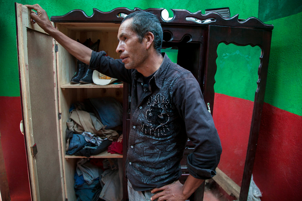 . Francisco Ramos Diaz, father of Gilberto Francisco Ramos Juarez, a Guatemalan boy whose decomposed body was found in the Rio Grande Valley of South Texas, shows the boy\'s clothing at thier home in San Jose Las Flores, northern Cuchumatanes mountains, Guatemala, Tuesday, July 1, 2014. The boy\'s birth certificate says he was 11 years old, but his father said Tuesday that the boy was really 15.  (AP Photo/Luis Soto)
