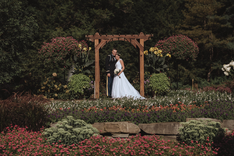 The bride and groom pose in a garden under an arbor.