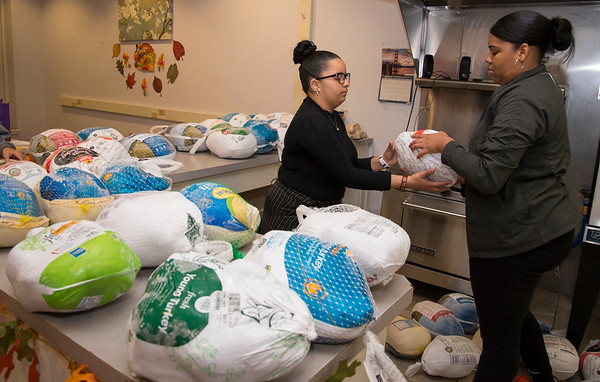11/25/19 Wesley Bunnell | StaffrrThanksgiving meals were handed out by HRA Bristol on Monday evening by workers and volunteers. Employee Taina Boria, L, receives help from volunteer Madelyn Torres with sorting the turkeys by size.
