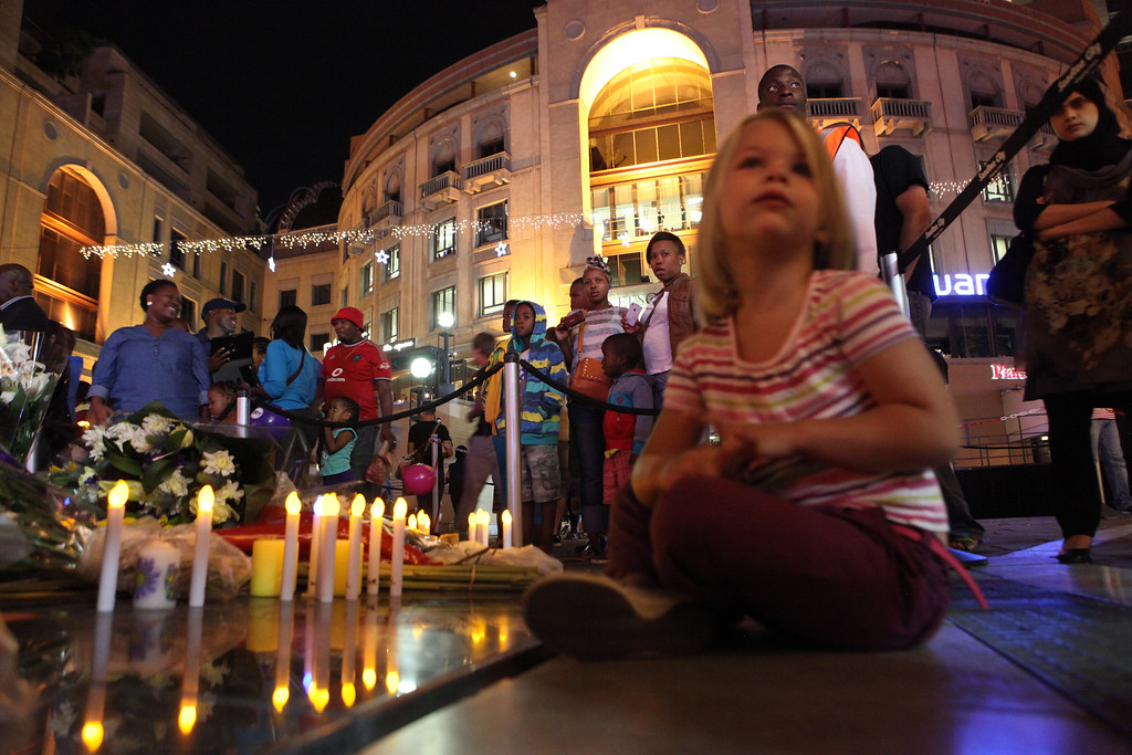 . A young girl sits next to candles and condolence messages for Nelson Mandela in Sandton, Johannesburg, South Africa, Saturday, Dec. 7, 2013. (AP Photo/Tsvangirayi Mukwazhi)