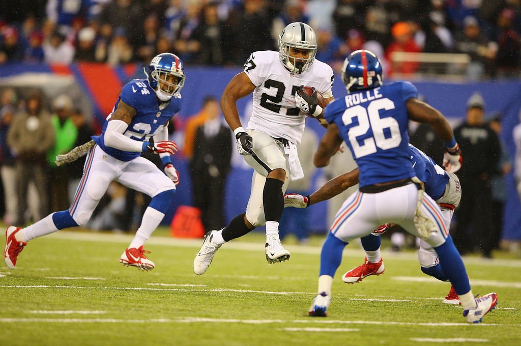 . Rashad Jennings #27 of the Oakland Raiders runs against  Antrel Rolle #26 of the New York Giants during their game at MetLife Stadium on November 10, 2013 in East Rutherford, New Jersey.  (Photo by Al Bello/Getty Images)