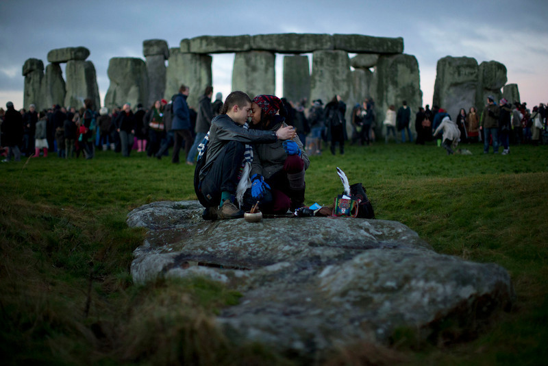 """. People embrace by the ancient stone circle of Stonehenge, in southern England, as access to the site is given to druids, New Age followers and members of the public on the annual Winter Solstice, Friday, Dec. 21, 2012. Doomsday hour is here and so still are we. According to legend, the ancient Mayans\' long-count calendar ends at midnight Thursday, ushering in the end of the world. Didn\'t happen. \""""This is not the end of the world. This is the beginning of the new world,\"""" Star Johnsen-Moser, an American seer, said at a gathering of hundreds of spiritualists at a convention center in the Yucatan city of Merida, an hour and a half from the Mayan ruins at Chichen Itza. (AP Photo/Matt Dunham)"""
