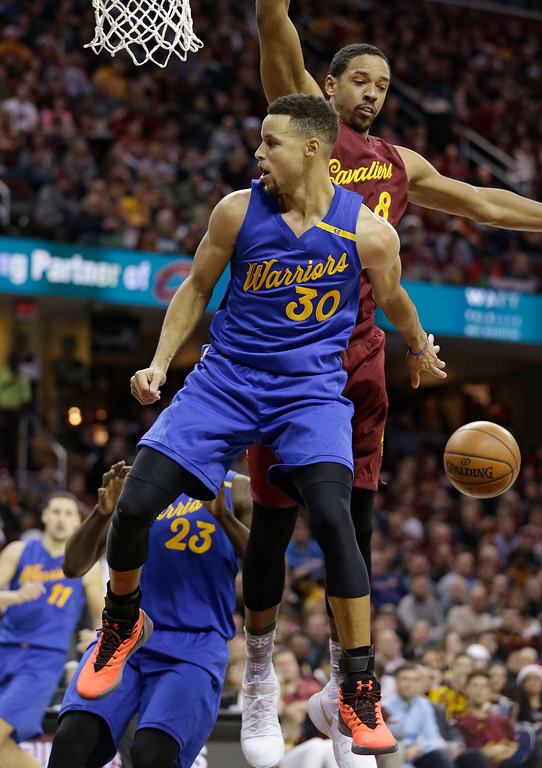 . Golden State Warriors\' Stephen Curry (30) passes around Cleveland Cavaliers\' Channing Frye (8) in the second half of an NBA basketball game, Sunday, Dec. 25, 2016, in Cleveland. The Cavaliers won 109-108. (AP Photo/Tony Dejak)