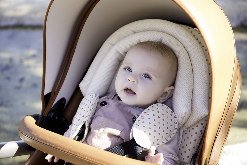Mima_Xari_Lifestyle_Camel_Aluminium_Chassis_Sandy_Beige_Starter_Pack_Baby_Looking_At_Camera_Close_Up.jpg