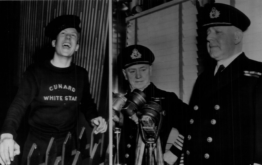 . Happily, Queen Elizabeth Crewman Derek foster, 16, laughs as the big ship ties up safely in New York.  At right, Chief Engineer William Sutcliffe (center) and Captain John C. Townley look quietly proud. 1940