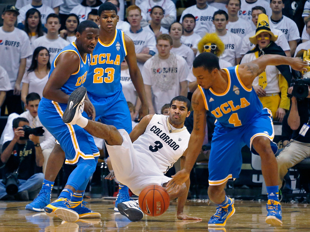 . UCLA\'s Norman Powell (4) dribbles off with the ball after stealing it from Colorado\'s Xavier Talton (3) during an NCAA college basketball game in Boulder, Colo., Thursday, Jan. 16, 2014. UCLA won 69-56. (AP Photo/Brennan Linsley)