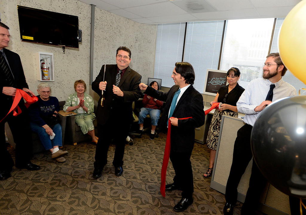 . LANG Vice President and CEO Michael Anastasi, left, and Sun Metro Editor Ryan Carter, right, perform a ribbon cutting ceremony during The Sun\'s Open House in downtown San Bernardino March 13, 2013.  GABRIEL LUIS ACOSTA/STAFF PHOTOGRAPHER.