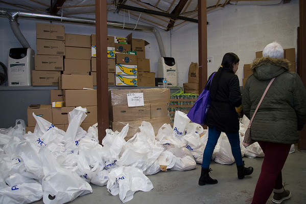 11/25/19 Wesley Bunnell | StaffrrThanksgiving meals were distributed by HRA workers and volunteers on Monday evening at their Osgood Park location. Clients walk past bags of potatoes and squash ready to be distributed.