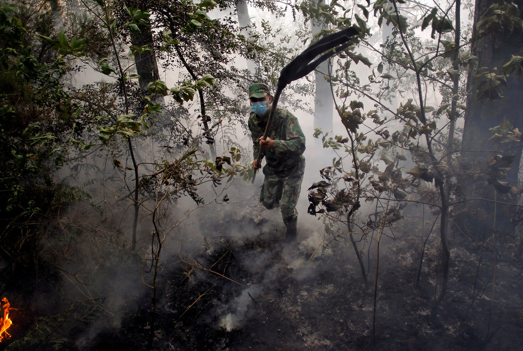 . A Portuguese military soldier uses a hoe to fight against a wildfire in Caramulo, north Portugal, Friday, Aug. 30, 2013. Firefighters continued to battle to quell one of several blazes still raging in the Serra do Caramulo on Friday, a day after a woman firefighter died fighting a forest fire in the area. (AP Photo/Francisco Seco)