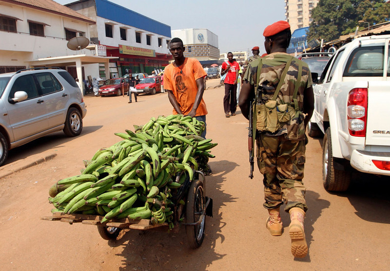 . A Central African Republic soldier walks past a vendor on a street in Bangui December 31, 2012. Central African Republic\'s embattled President Francois Bozize said on Sunday he was ready to share power with the leaders of a rebellion that has swept aside government defences to within striking distance of the capital Bangui. REUTERS/Luc Gnago