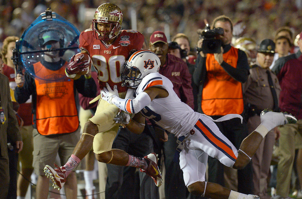 . Florida State\'s Rashad Greene is knocked out of bounds by Auburn\'s Ryan White during the first half of the 2014 Vizio BCS National Championship January 6, 2014 in Pasadena CA.(Andy Holzman/Los Angeles Daily News)