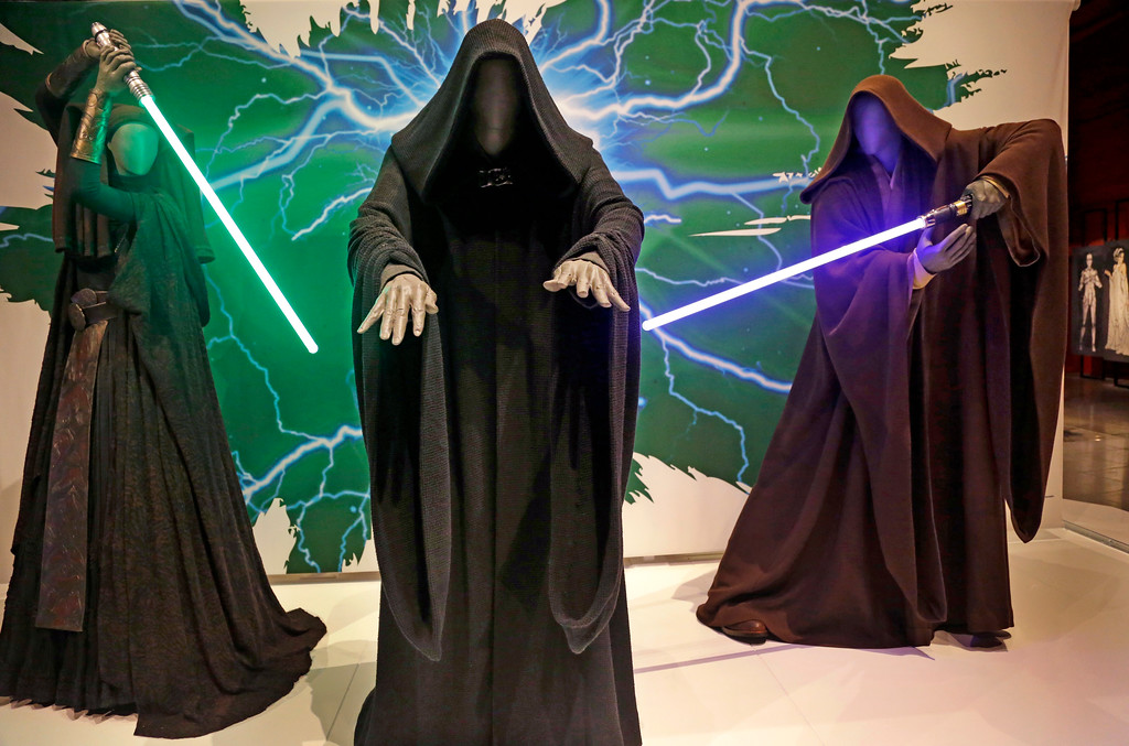 . In this photo taken Thursday, Jan. 29, 2015, Sith robes and lightsabers are displayed as part of an exhibit on the costumes of Star Wars at Seattle�s EMP Museum. The creators of the new exhibit, with 60 original costumes from the six Star Wars movies, are hoping to gather geeks, fashionistas and movie fans together to discuss how clothing helps set the scene. The exhibit, �Rebel, Jedi, Princess, Queen: Star Wars and the Power of Costume,� will be in Seattle through early October and then travel across the United States through 2020. (AP Photo/Elaine Thompson)