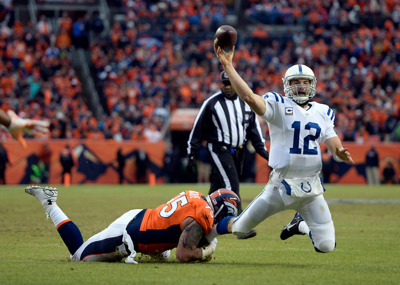 . Andrew Luck (12) of the Indianapolis Colts gets rid of the ball as he is taken down by Derek Wolfe (95) of the Denver Broncos during the second quarter.  The Denver Broncos played the Indianapolis Colts in an AFC divisional playoff game at Sports Authority Field at Mile High in Denver on January 11, 2015. (Photo by Brent Lewis/The Denver Post)