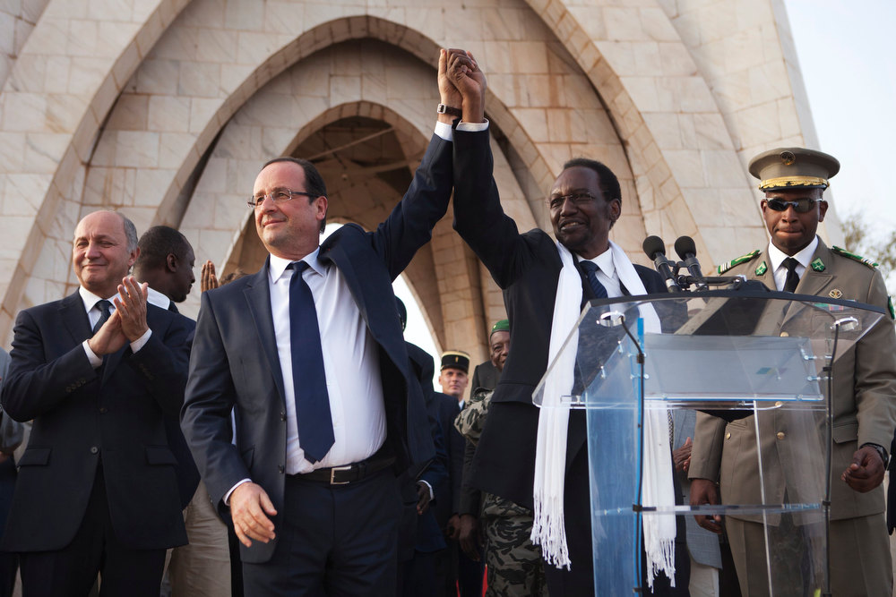 . France\'s President Francois Hollande (2nd L) joins hands with Mali\'s interim president Dioncounda Traore after Traore spoke at Independence Plaza in Bamako, Mali February 2, 2013. France will withdraw its troops from Mali once the Sahel state has restored sovereignty over its national territory and a U.N.-backed African military force can take over from the French soldiers, Hollande said on Saturday. REUTERS/Joe Penney