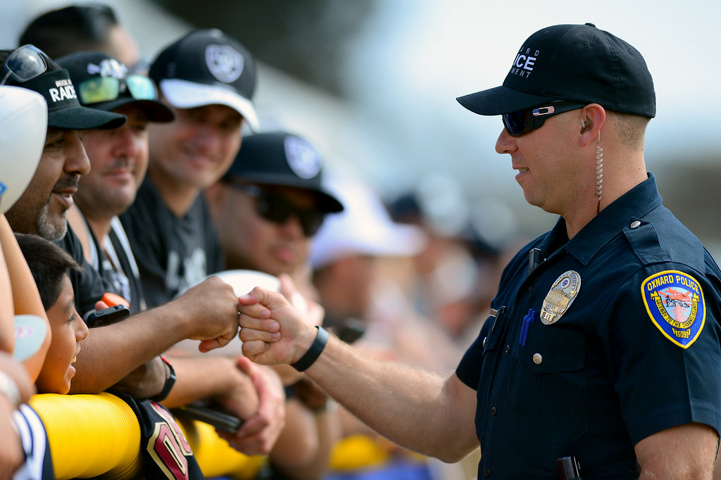 . An Oxnard police officer greets Raider fans at the Cowboys-Raiders practice in Oxnard, Wednesday, August 13, 2014. (Photo by Michael Owen Baker/Los Angeles Daily News)