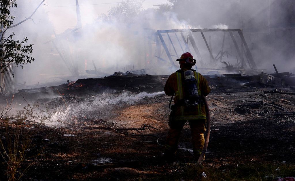 . A firefighter cools off some hot spots from a four-alarm fire along the 700 block of Seventh Street in San Bernardino August 18, 2013.  The fire displaced dozens of people from an apartment complex.  GABRIEL LUIS ACOSTA/STAFF PHOTOGRAPHER.