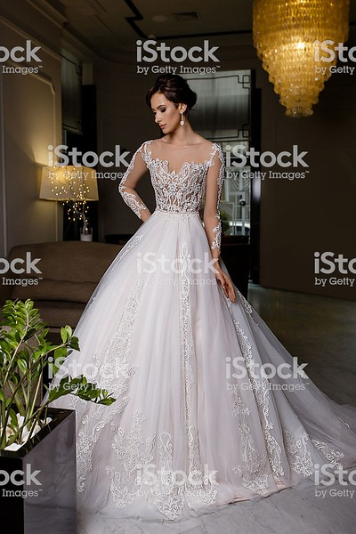 Serious young brunette model female poses in long bridal dress with lace on charming background