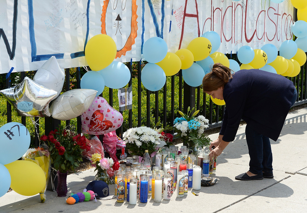 . Maria Avila, the mother of a student at El Monte High School, places a candle at a memorial near the front gate of the school. Students at El Monte High School brought flowers, candles and other items in remembering Adrian Castro, a Senior student who was killed in bus crash in Northern California that took the lives of 10 people. El Monte, CA. 4/13/2014(Photo by John McCoy / Los Angeles Daily News)
