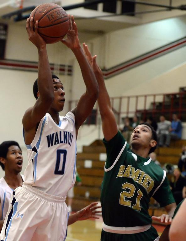 . Walnut\'s Zuri Williams (0) drives to the basket past Damien\'s Tyler Ginyard (21) in the first half of the Glendora basketball tournament at Glendora High School in Glendora, Calif., on Friday, Dec. 13, 2013. Damien won 66-60.  (Keith Birmingham Pasadena Star-News)